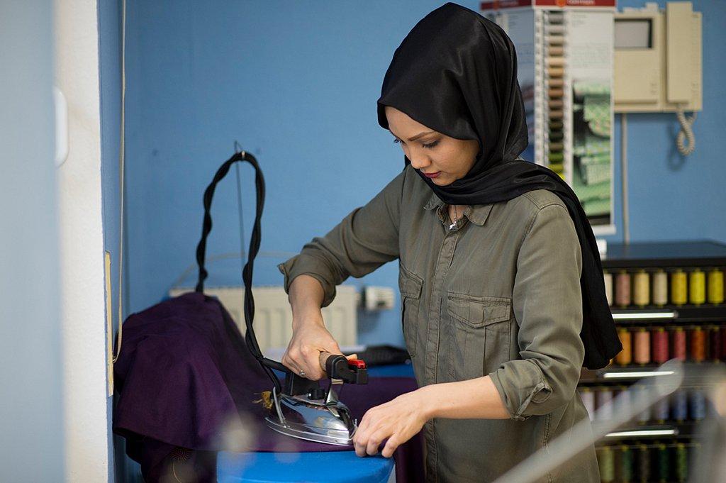 Schneiderin bei der Arbeit in der Werkstatt Stitch by Stitch.